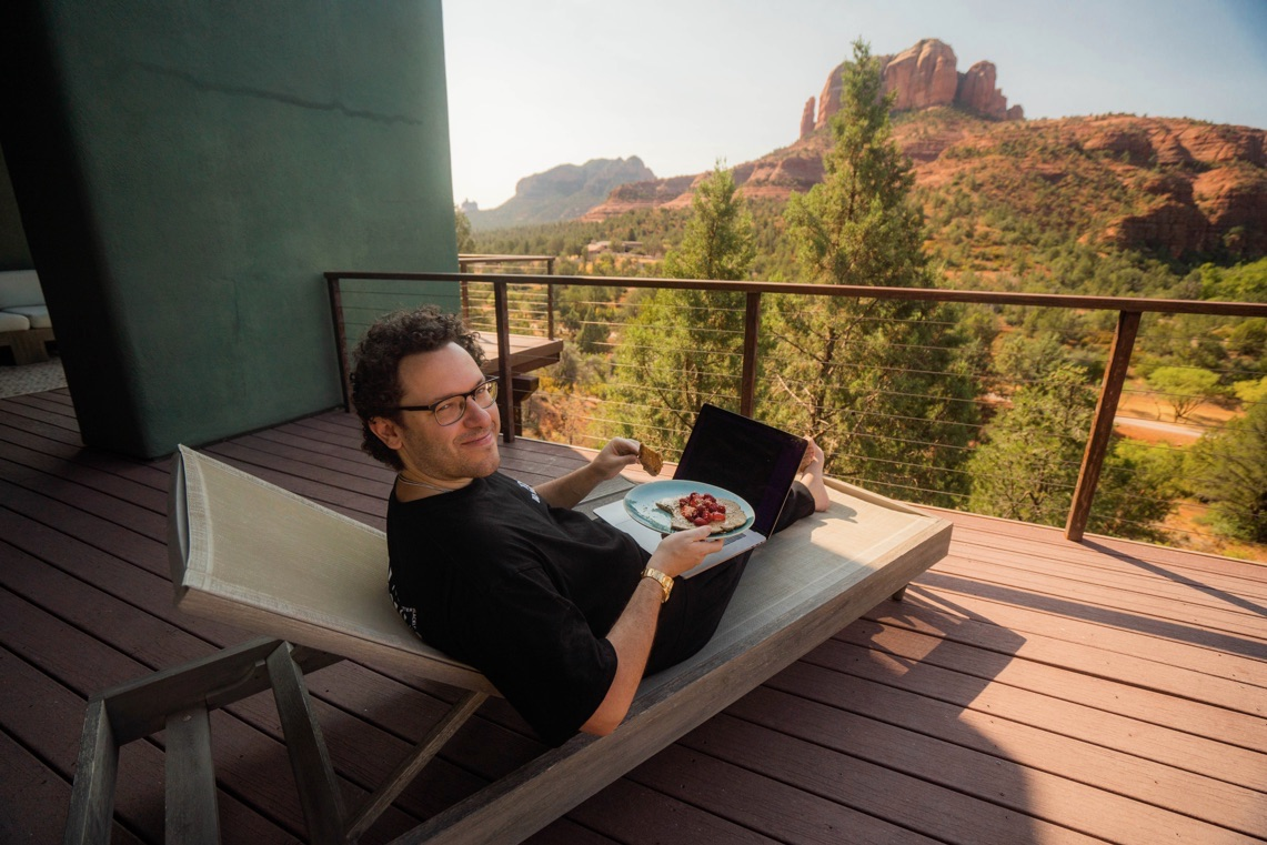 tim sykes lounging in arizona with laptop and food on lap