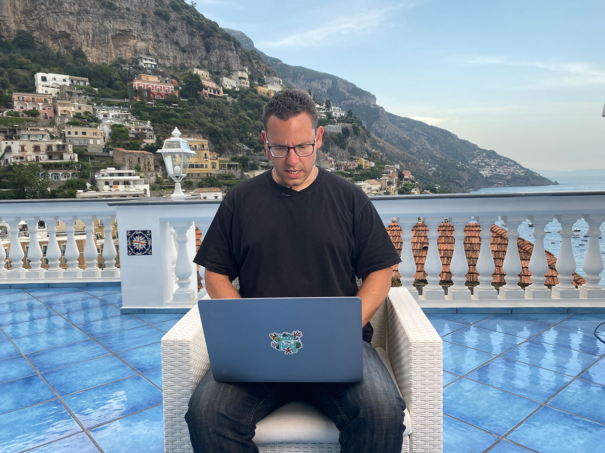 Tim Sykes checking his top penny stocks list in Italy